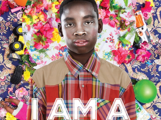 A boy wearing a plaid shirt standing against a floral background