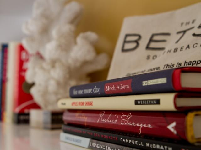 A stack of books on a dresser.