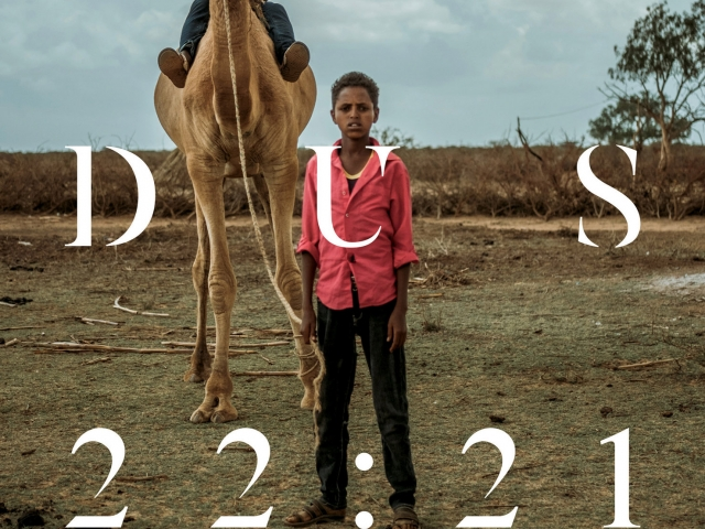 A boy standing tall while another boy is riding a camel