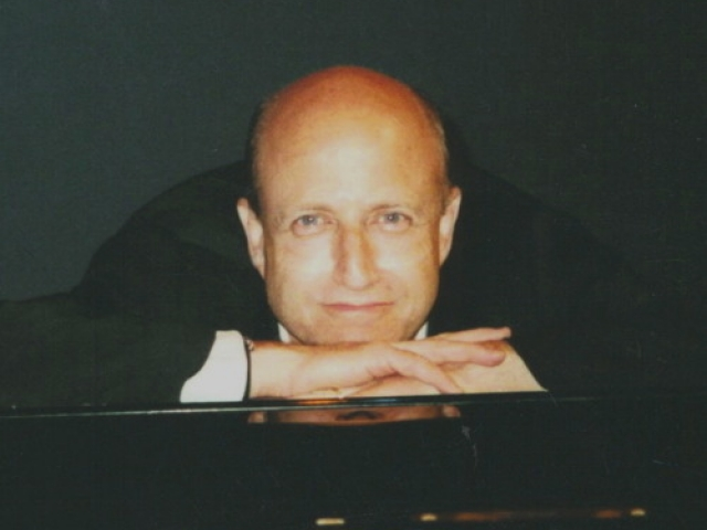 marc irwin portrait as he leans on a piano