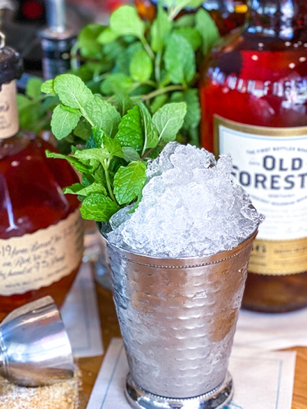 Set up of Mint Julep ingredients including bourbon, mint, and crushed ice.