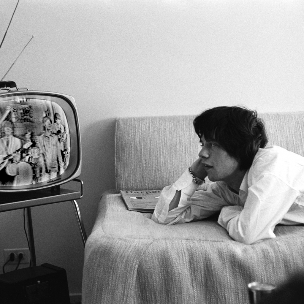 Mick Jagger watching television while lying down on the sofa