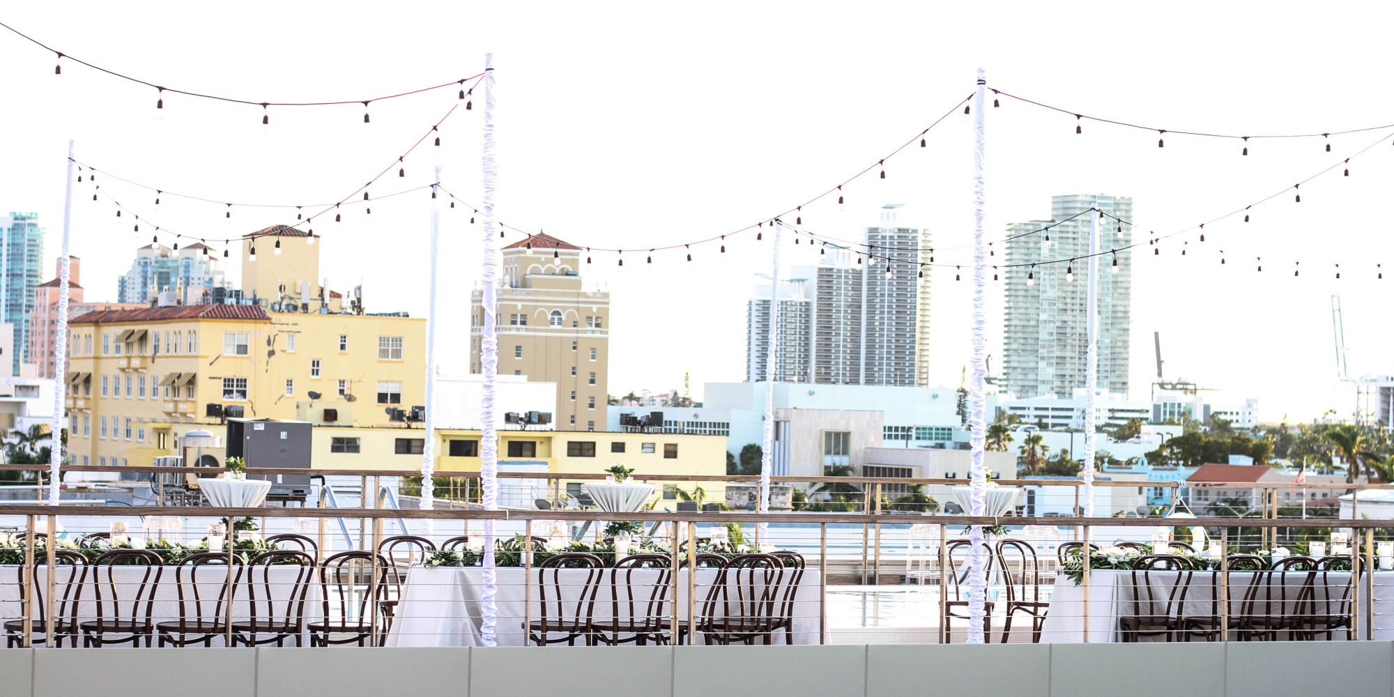 Tables set beside a rooftop pool deck.