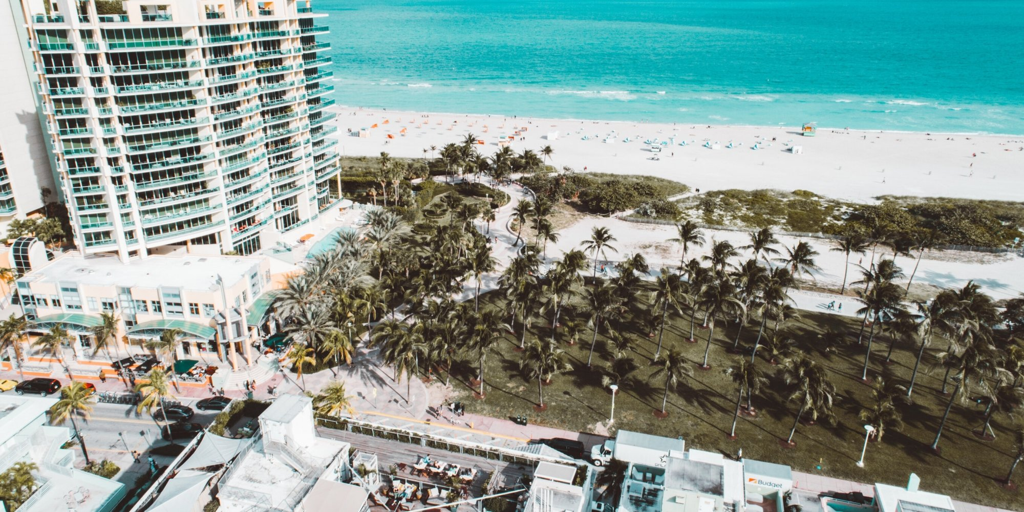Drone photo overlooking Miami Beach with building, water, and palm trees.